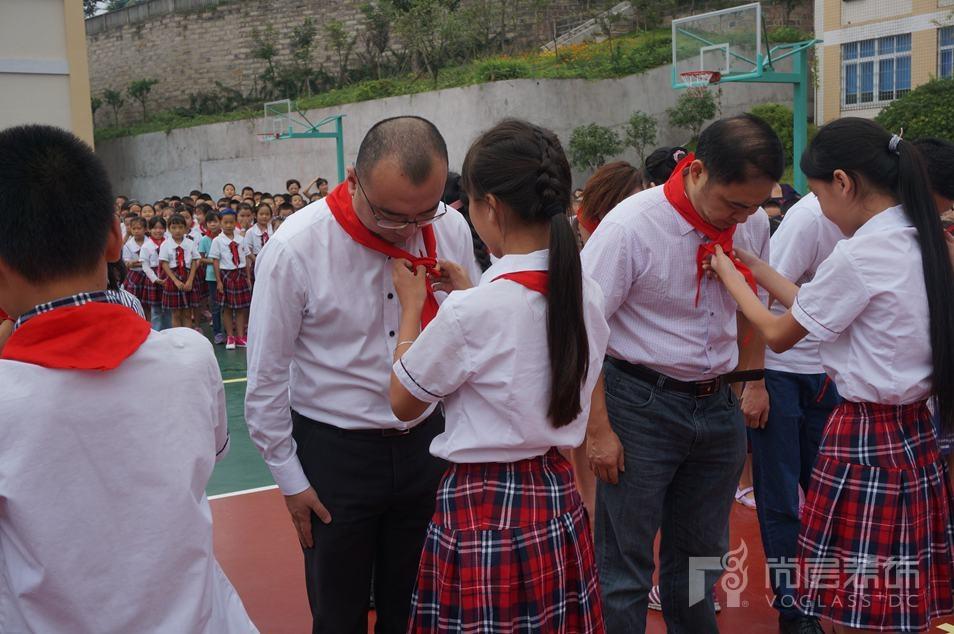 四川内江乐贤尚层希望小学少先队员为嘉宾佩戴红领巾