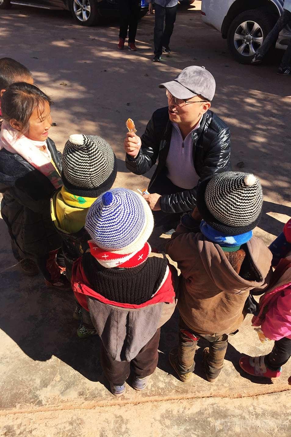 尚层工作人员分享糖果给孩子们