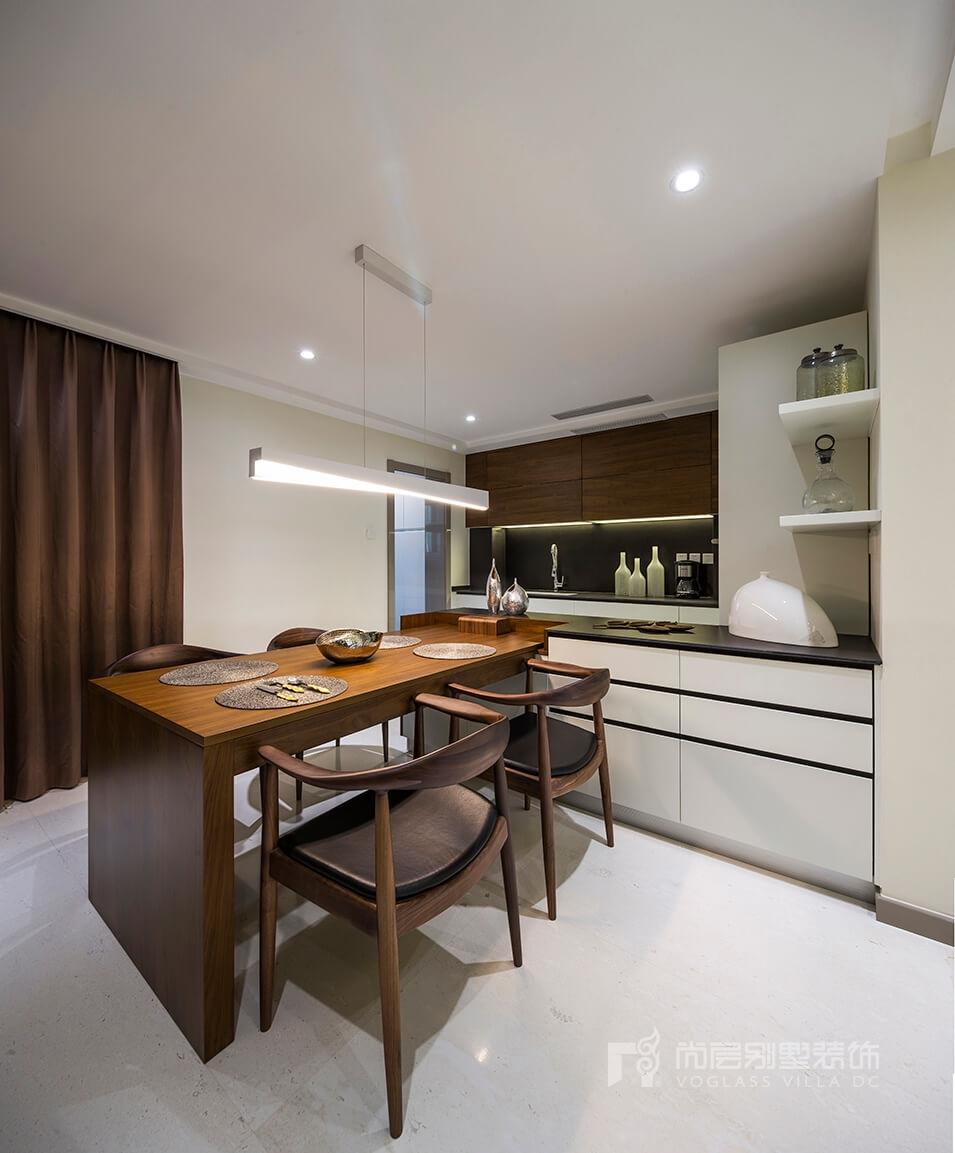 西餐厨房与胡桃木餐桌相连,苏茜白的西厨柜面与深咖色胡桃木温润相接